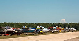 single prop airplanes parked beside runway